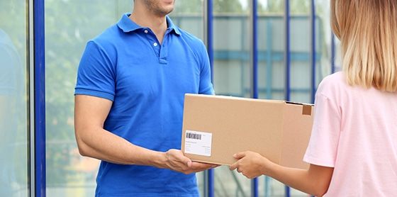 stock-photo-woman-receiving-parcel-from-delivery-service-courier-outdoors-1240823413